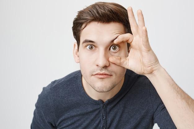 Zabawny facet rozszerza oko, żeby go zeskanować
