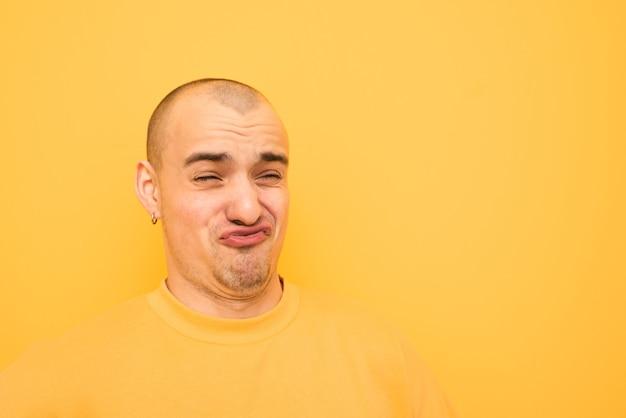 Zabawny facet w kolczykach i łysej głowie na głowie w żółtej sukience