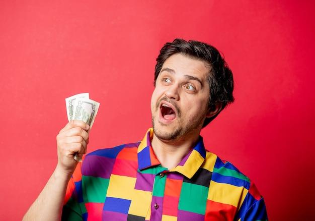 Zabawny facet w koszuli w stylu lat 80-tych trzymający pieniądze w ręku na czerwonym backgorundzie