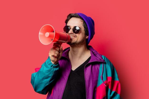 Zabawny facet w kurtce i okularach przeciwsłonecznych w stylu lat 80. trzyma megafon na czerwonym backgorundzie