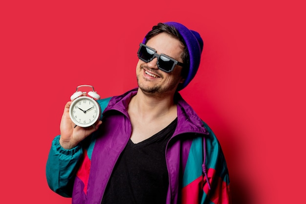 Zabawny facet w kurtce i okularach przeciwsłonecznych w stylu lat 80-tych trzyma budzik na czerwonym backgorundzie
