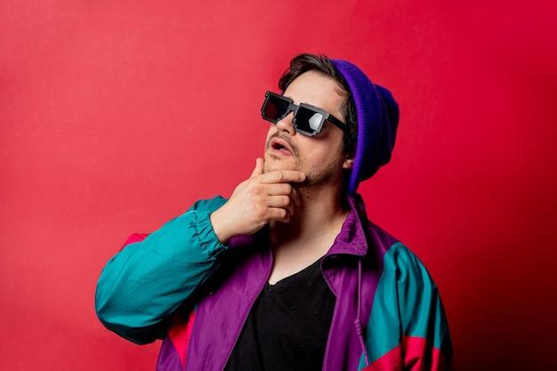 Zabawny facet w kurtce w stylu lat 80-tych i okularach przeciwsłonecznych na czerwonym backgorundzie