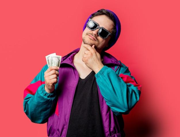 Zabawny facet w kurtce w stylu lat 80-tych i okularach przeciwsłonecznych trzyma pieniądze na czerwonym backgorundzie