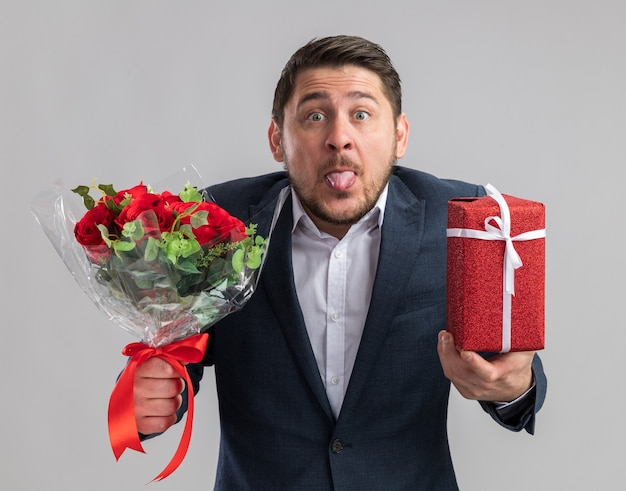 Zabawny i radosny młody przystojny mężczyzna ubrany w garnitur z bukietem róż i prezentem na walentynki wystającym językiem