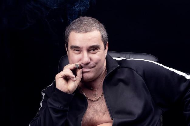 Zabawny i uroczy dorosły biały człowiek pali cygaro, śmieje się i uśmiecha patrząc w kamerę. uśmiech rosyjskiego bandyty mafijnego