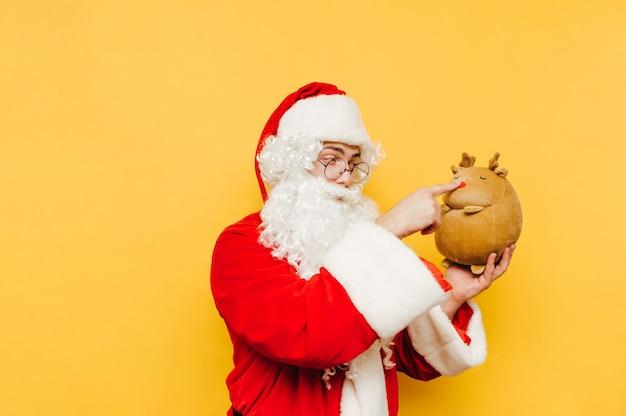 Zabawny i uroczy święty mikołaj trzyma w ręku wypchaną zabawkę renifera