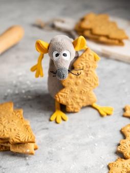Zabawny i uroczy szczur zabawkowy (symbol 2020) z żółtymi uszami kradnącymi piernikowe ciasteczko w kształcie choinki, może służyć jako kartka świąteczna i noworoczna, zima.