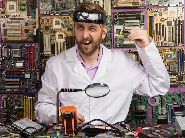 Zabawny inżynier w białym fartuchu trzymający śrubokręt w uchu, siedząc przy stole w swoim laboratorium