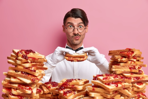 Zabawny kelner w śnieżnobiałej koszuli i rękawiczkach, głodny po długiej pracy, trzyma pyszną kanapkę, otoczony wieloma grzankami, nosi okrągłe okulary, nie przestrzega diety, ma dobry apetyt