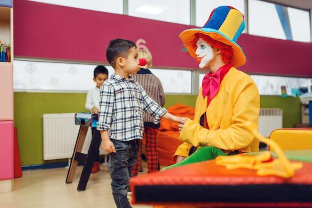 Zabawny klaun i mały chłopiec z czerwonym nosem bawią się razem.