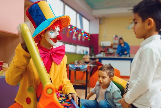 Zabawny klaun z radosnymi dziećmi bawiącymi się alfabetem na pokładzie.