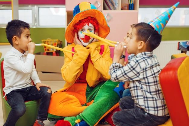 Zabawny klaun z wesołymi dziećmi razem dmucha do rur.