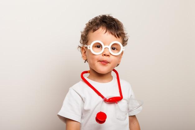 Zabawny kręcone dziecko w okularach ze stetoskopem na szyi gra lekarza. większy portret dziecka wykonującego zawód lekarza.