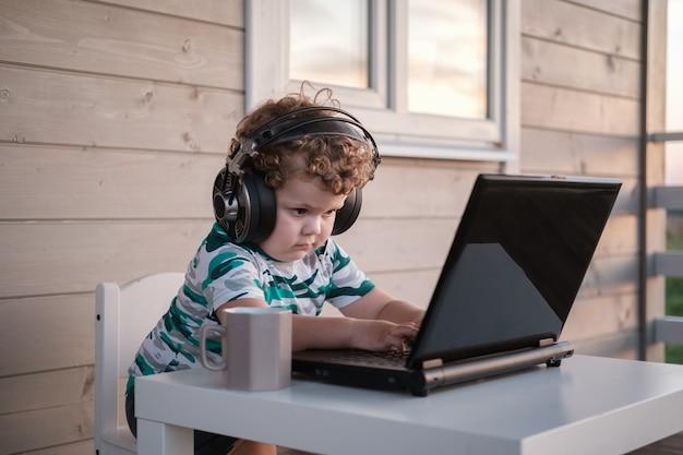 Zabawny ładny chłopak z kręconymi włosami w dużych słuchawkach siedzący przy laptopie