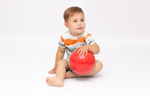 Zabawny ładny mały chłopczyk ubrany w pasiaste body, siedzący i grający w nową piłkę na białej powierzchni