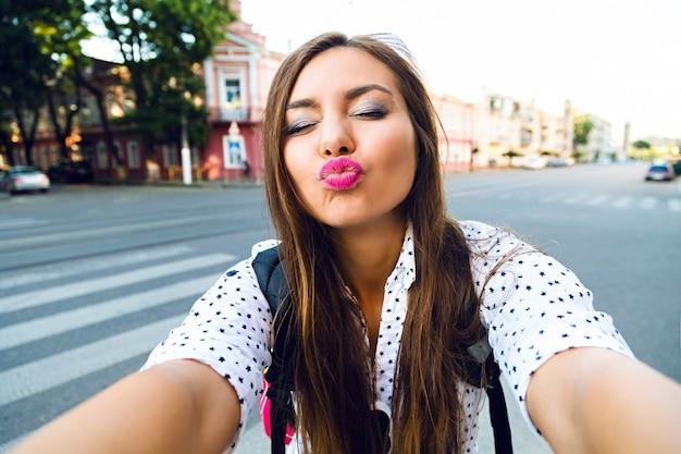 Zabawny letni obraz młodej dziewczyny ładnej podróżniczki podejmowania selfie na ulicy, wysyłając pocałunek do ciebie, pozytywny nastrój