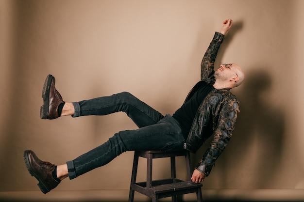 Zabawny łysy mężczyzna w skórzanej kurtce motocyklowej i butach oxford. stylowy dziwny chłopak spada z krzesła.