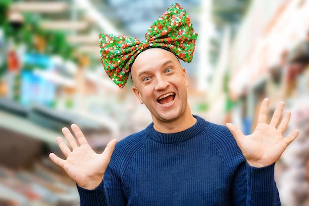 Zabawny łysy mężczyzna z kokardą na głowie, świąteczny nastrój