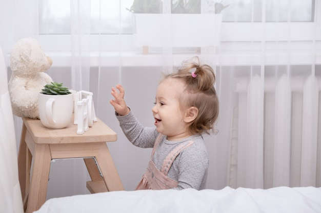 Zabawny maluch dziewczyna bawi się zabawkami w domu w białym pokoju.