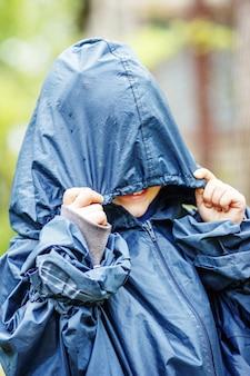 Zabawny mały chłopiec chodzi w deszczu w płaszczu przeciwdeszczowym z kapturem na zewnątrz