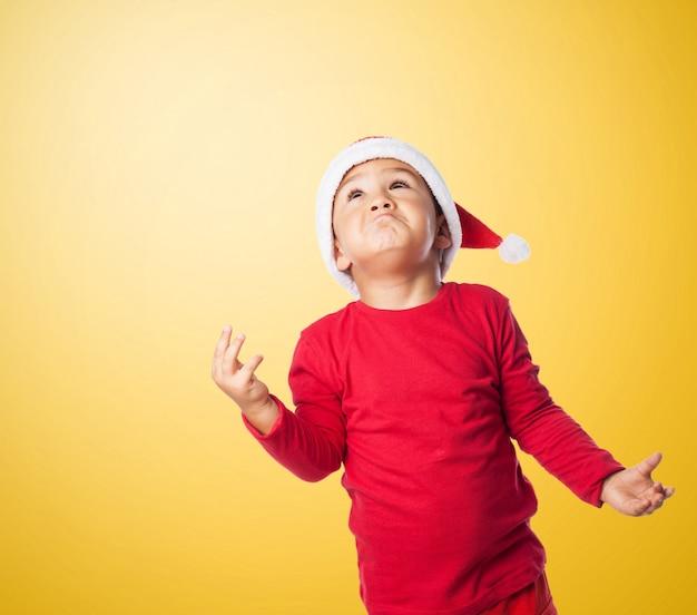 Zabawny mały chłopiec gestykulując rękami