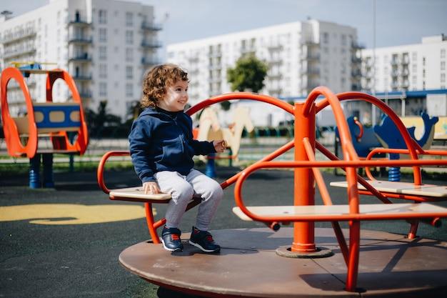Zabawny mały chłopiec na pustym placu zabaw podczas kwarantanny bez ochrony