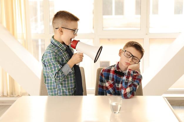 Zabawny mały chłopiec z megafonem krzyczący na swojego znudzonego przyjaciela siedzącego przy stole
