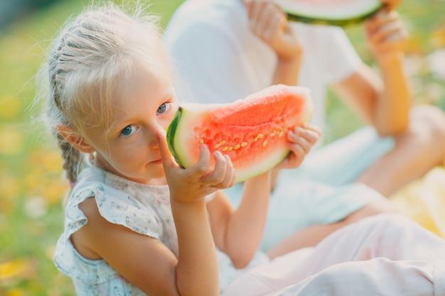 Zabawny mały maluch dzieci brat i siostra jedzenie arbuza w parku. szczęśliwy chłopiec i dziewczynka razem. dzieciństwo, rodzina, koncepcja zdrowej diety.