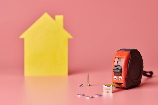 Zabawny metalowy centymetr. remont domu remont domu i odnowiona koncepcja. postać w kształcie żółtego domu na różowo.