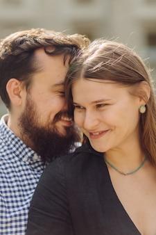 Zabawny mężczyzna i kobieta cieszący się spędzaniem wolnego czasu razem stojąc na zewnątrz i śmiejąc się