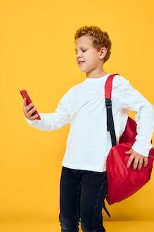 Zabawny mężczyzna nastolatek w białej bluzie telefon komórkowy czerwony plecak żółtym tle