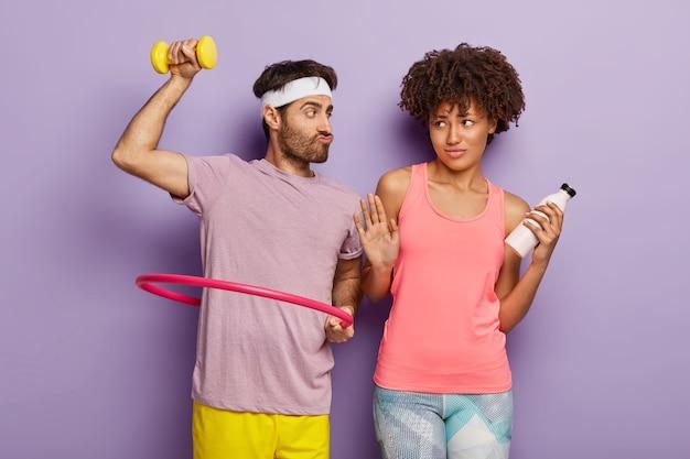 Zabawny mężczyzna podnosi hantle, pozuje z hula-hopem, sugeruje dziewczynie spróbowanie aerobiku, ciemnoskóra kobieta robi gest odmowy, trzyma butelkę ze świeżą wodą. para mieszanej rasy razem uprawia sport