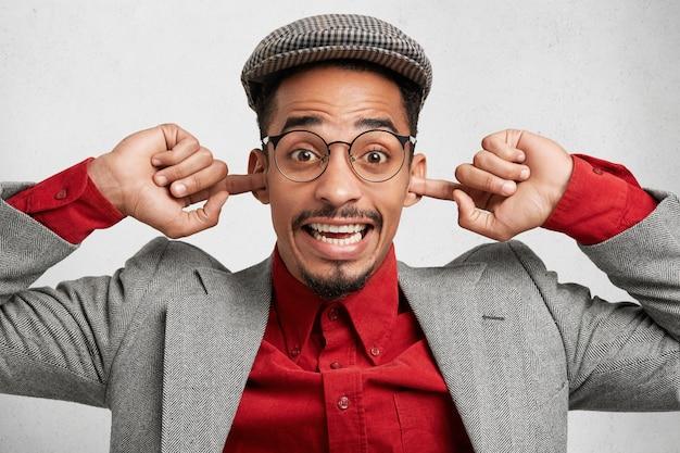 Zabawny mężczyzna rasy mieszanej ma na sobie czapkę i czerwoną koszulę z marynarką, zatyka uszy i radośnie się uśmiecha