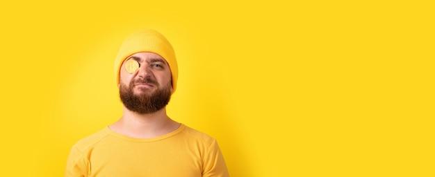 Zabawny mężczyzna z bitcoinami na żółtym tle, układ panoramiczny