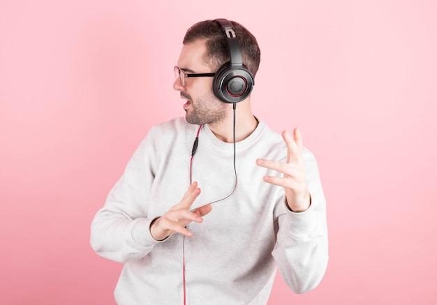 Zabawny mężczyzna z brodą i białą bluzą słucha muzyki w słuchawkach, śpiewa i tańczy na różowym tle. odosobniony.
