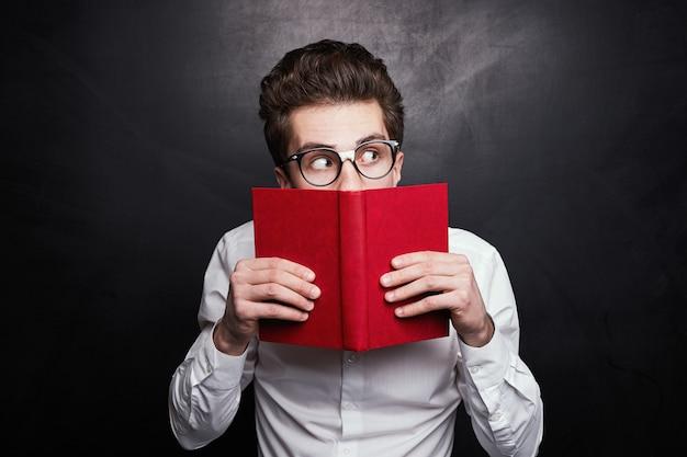 Zabawny mężczyzna z książką wyglądający podejrzanie