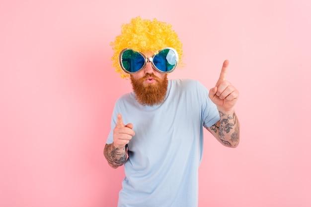 Zabawny mężczyzna z żółtymi tańcami peruke i okularów przeciwsłonecznych