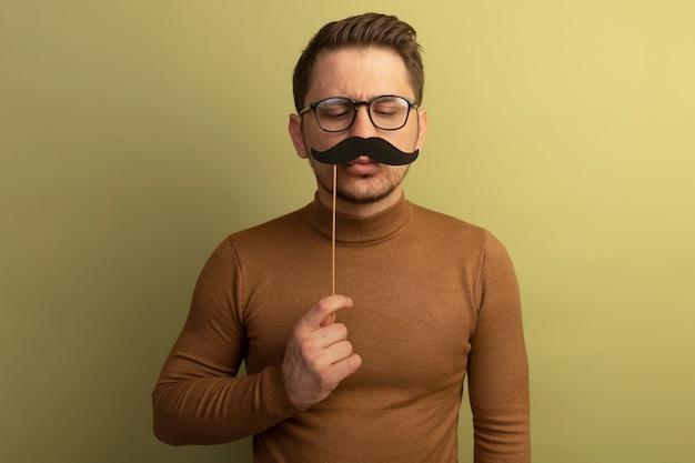 Zabawny młody blond przystojny mężczyzna w okularach, trzymając fałszywe wąsy na patyku nad ustami, patrząc w dół na wąsy na białym tle na oliwnej ścianie