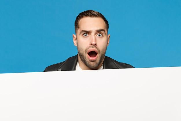 Zabawny młody brodaty mężczyzna wypatruje duży biały pusty pusty billboard dla treści promocyjnych na białym tle na tle niebieskiej ściany portret studio. koncepcja życia szczere emocje ludzi. makieta miejsca na kopię.