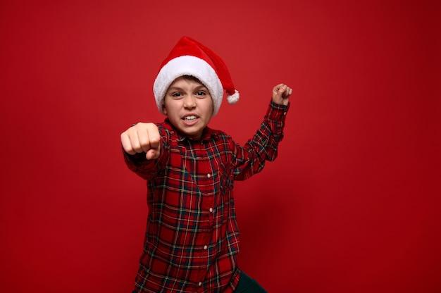 Zabawny młody chłopak ubrany w koszulę w kratę i czapkę świętego mikołaja, pokazując pięść, patrząc w kamerę, pozowanie na czerwonym tle z miejscem na kopię na boże narodzenie i nowy rok reklama