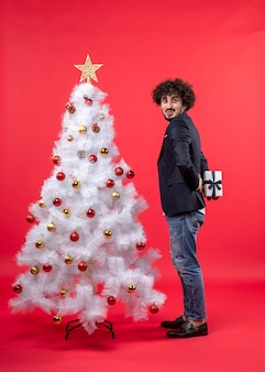 Zabawny młody człowiek trzyma prezent za stojącym w pobliżu udekorowanego białego drzewa xmas po prawej stronie czerwieni