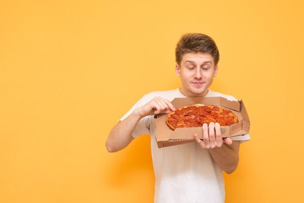 Zabawny młody człowiek trzyma pudełko świeżej pizzy i cieszy się jej aromatem