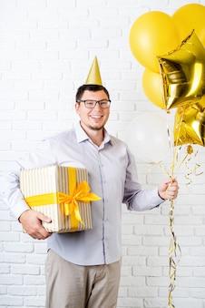Zabawny młody człowiek ubrany urodziny kapelusz trzymając balony