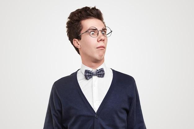 Zabawny młody człowiek w okrągłych okularach odwracający wzrok ze zdumienia na szarym tle