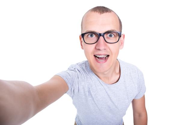 Zabawny młody człowiek w okularach z szelkami na zębach robi zdjęcie selfie na białym tle
