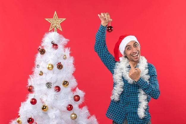 Zabawny młody człowiek z czapką świętego mikołaja w niebieskiej koszuli w paski i podnoszący pokazujący element dekoracyjny stojący w pobliżu drzewa xsmas na czerwono