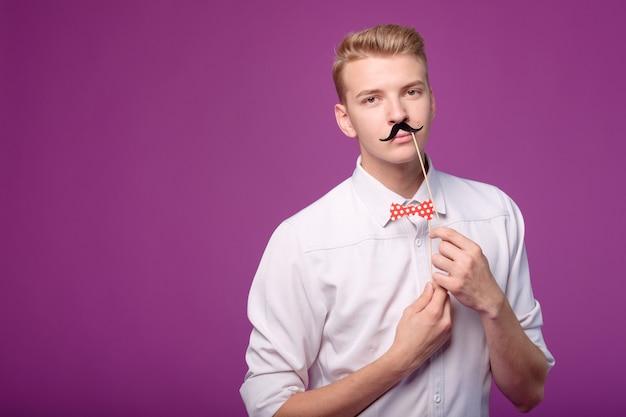 Zabawny młody człowiek z papierowym wąsem i krawatem motyla na tle
