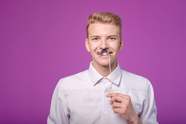 Zabawny młody człowiek z papierowymi wąsami na tle
