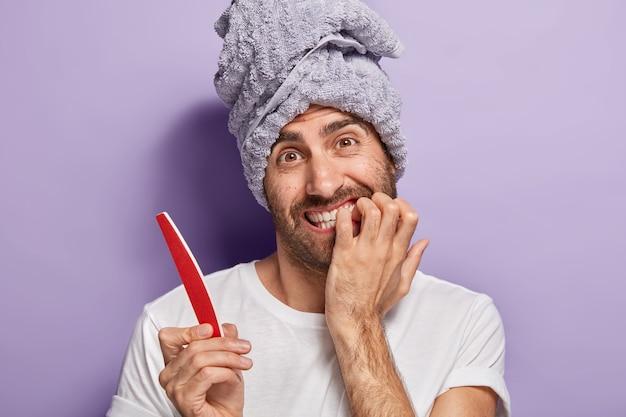 Zabawny młody europejczyk obgryza paznokcie, próbuje samodzielnie wykonać manicure, trzyma pilnik do paznokci, nosi biały casualowy t-shirt, poddaje się zabiegom kosmetycznym przed ważnym spotkaniem lub randką z dziewczyną