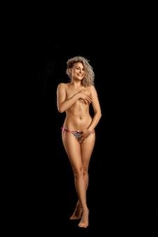 Zabawny młody model blondynka w majtki pozowanie w studio i uśmiechnięty